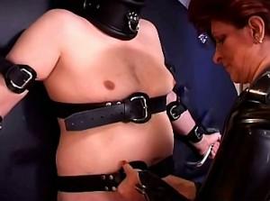 Ongenadig harde domina bind haar slaaf aan het wiel
